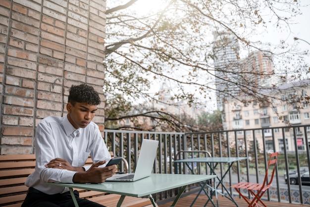 Un homme noir est assis sur une terrasse d'été ou une véranda près d'un café. le gars travaille sur un ordinateur portable et utilise un smartphone. vue du centre-ville d'affaires de printemps
