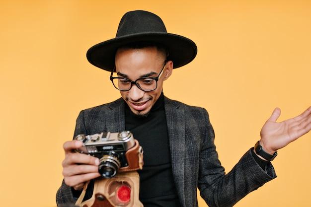 Homme noir étonné au chapeau regardant la caméra. portrait de photographe masculin africain émotionnel debout sur le mur jaune.