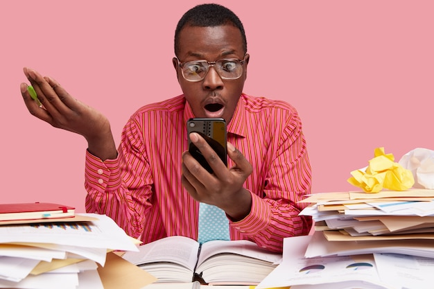 Un homme noir étonné regarde l'écran du téléphone portable et lit des nouvelles choquantes