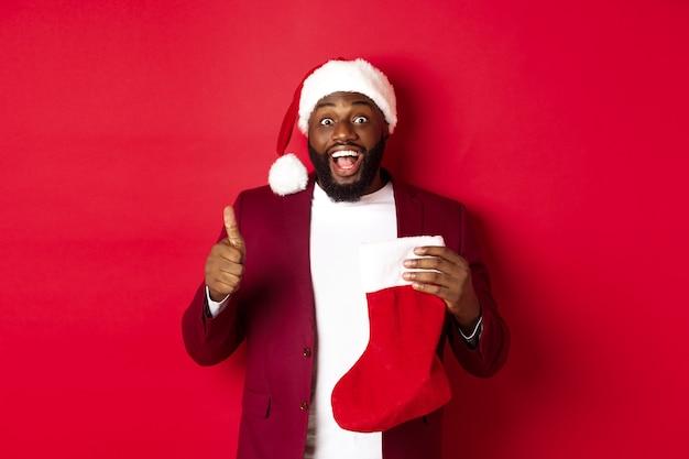 Homme noir excité montrant le pouce levé en signe d'approbation, tenant une chaussette de noël avec des cadeaux de vacances, souriant étonné, debout sur fond rouge