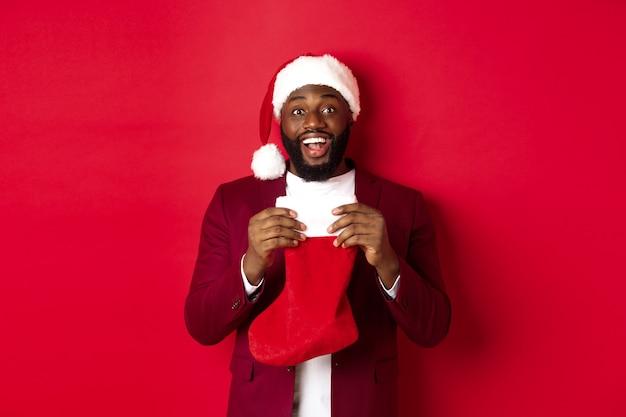 Un homme noir excité ouvre la chaussette de noël avec des cadeaux et des bonbons, souriant heureux, debout en bonnet de noel sur fond rouge.