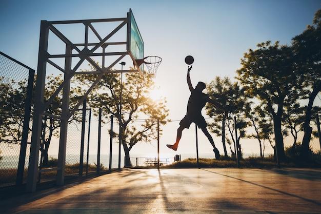 Homme noir, faire du sport, jouer au basket au lever du soleil, sauter silhouette