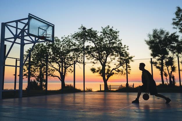 Homme noir, faire du sport, jouer au basket au lever du soleil, silhouette