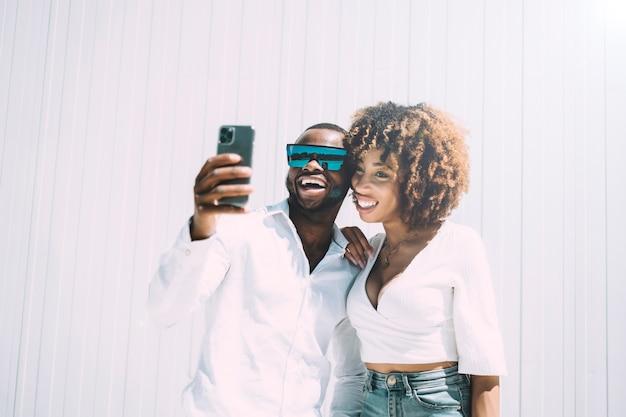 Homme noir et femme afro faisant un autoportrait avec un smartphone.