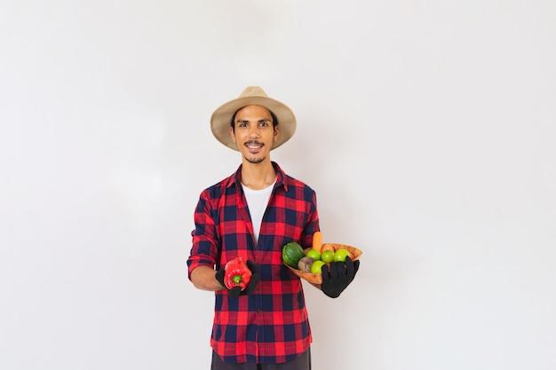 Homme noir fermier avec chapeau et gants tenant un panier de légumes (carotte, citron, tomates, chayote et betterave) isolé en fond blanc