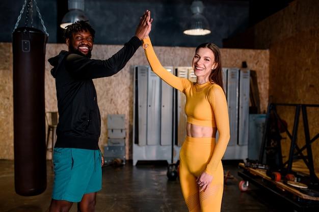 Un homme noir et une fille font du sport. ils se battent un cinq