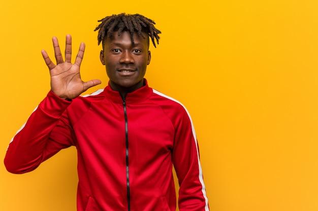 Homme noir de fitness jeune souriant joyeux montrant le numéro cinq avec les doigts.