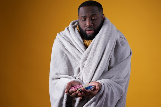 Homme noir a froid, tenant des pilules dans les mains.
