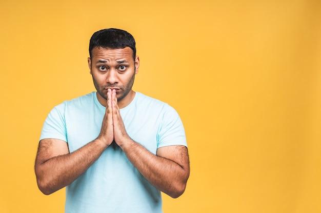 Un homme noir indien américain portant une position décontractée sur un fond jaune isolé mendiant et priant avec les mains avec une expression d'espoir sur un visage très émotif et inquiet.