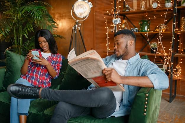 Homme noir lisant le journal, sa femme à l'aide de téléphone portable sur la table,
