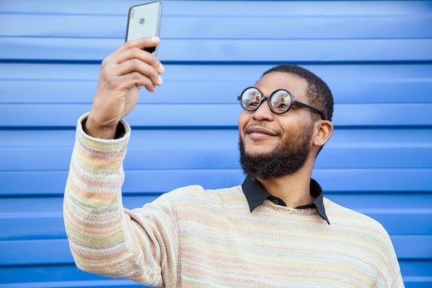 Homme noir avec des lunettes rondes de nerd, prenant un selfie avec votre téléphone portable. un mur de rue bleu en arrière-plan.