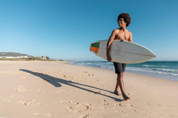 Homme noir marchant le long de la plage avec planche de surf