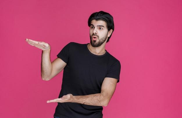 L'homme en noir montre les dimensions estimées d'un colis