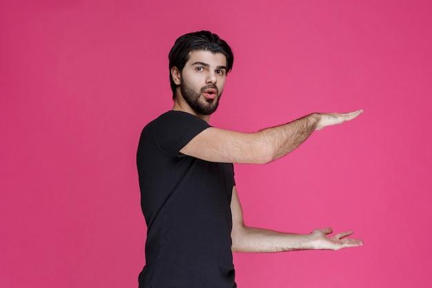 L'homme En Noir Montre Les Dimensions Estimées D'un Colis Photo gratuit