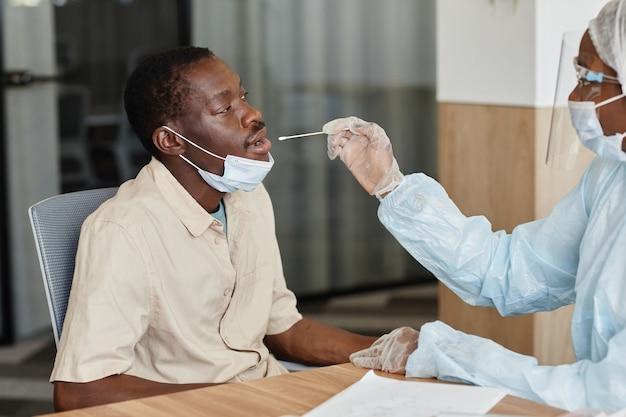 Homme noir ouvrant la bouche pour laisser le médecin prélever un écouvillon nasal pour prélever un échantillon pour le test de covid