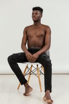 Homme noir plein coup sur chaise posant