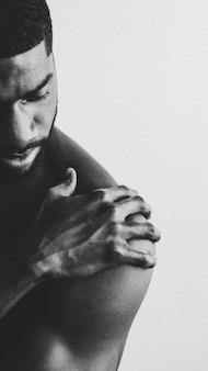 Homme noir à la poitrine nue touchant son épaule