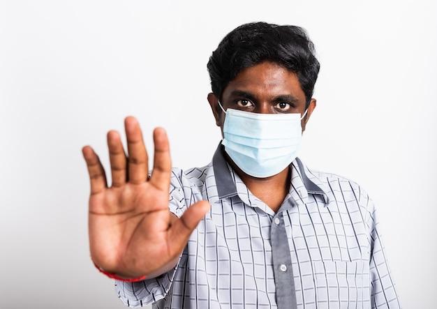 Homme noir portant un masque protecteur contre le coronavirus et levant le panneau d'arrêt de la main