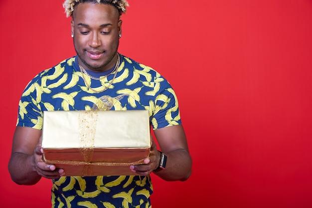 Un homme noir a reçu un cadeau une surprise tient un korobuka dans ses mains avec un regard surpris