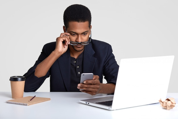Un homme noir surpris détient un téléphone mobile, lit un message texte avec étonnement, regarde à travers des lunettes, enregistre dans le bloc-notes