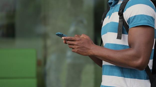 Homme noir tapant sur un smartphone dans la rue homme utilisant un téléphone portable à l'extérieur gars portant un tshirt en tapant un message