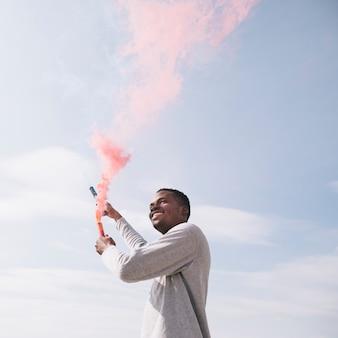 Homme noir tenant des bombes de fumée rouge