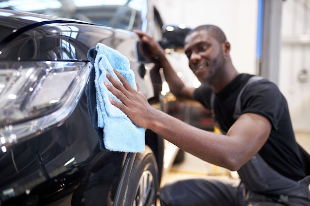 L'homme noir tient la microfibre à la main et polit la voiture en service automobile