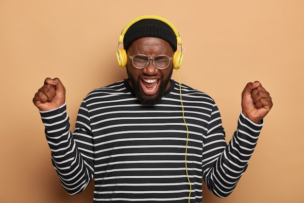 Un homme noir trop émotif danse avec les poings levés, porte des écouteurs sur les oreilles