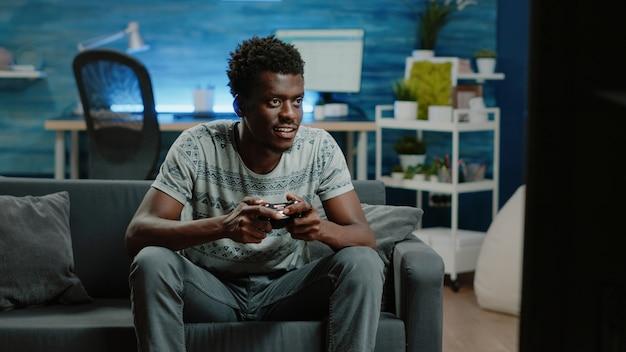 Homme noir utilisant un contrôleur et une console pour jouer à des jeux vidéo