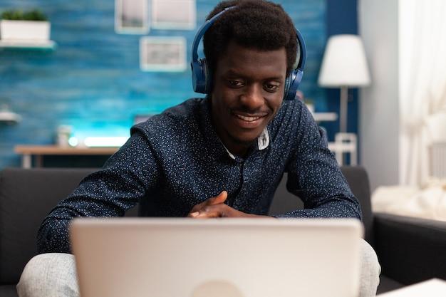 Homme noir utilisant des écouteurs et la technologie d'ordinateur portable