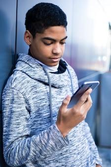 Un homme noir utilise un téléphone portable. adolescent assis sur les marches jouant à un jeu sur le smartphone. un garçon afro-américain écrit un message.