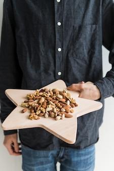 Homme avec des noix sur une planche à découper