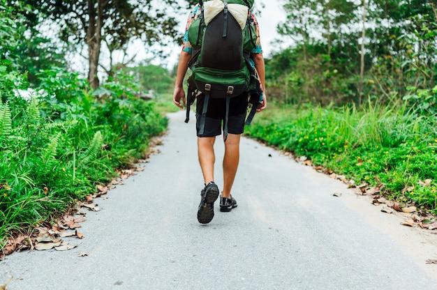 Homme nomade numérique marchant sur la route forestière