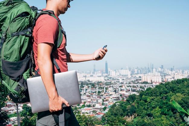 Homme nomade numérique parcourant le monde en travaillant avec un smartphone