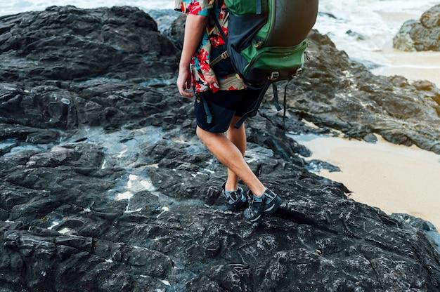 Homme nomade numérique sur la plage avec sac à dos
