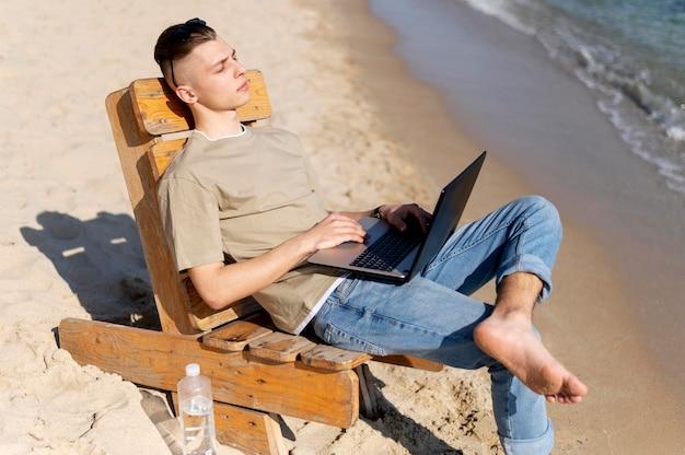 Homme nomade plein coup travaillant sur la plage