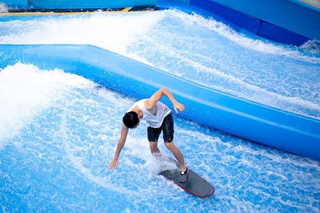 Homme non identifié pratiquant une planche de surf dans un sport extrême.