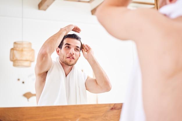Homme non rasé peignant les cheveux debout près du miroir dans la salle de bain