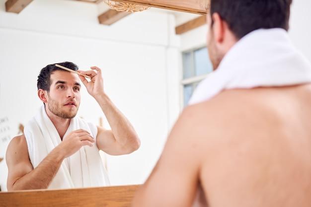 Homme non rasé se peignant les cheveux en se tenant debout avec une serviette blanche sur le cou près du miroir dans la salle de bain