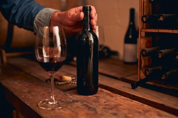Homme non reconnu mettant sa main sur un goulot de bouteille. verre de vin rouge debout près de table en bois