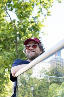 Homme nordique avec barbe et lunettes de soleil souriant dans le parc