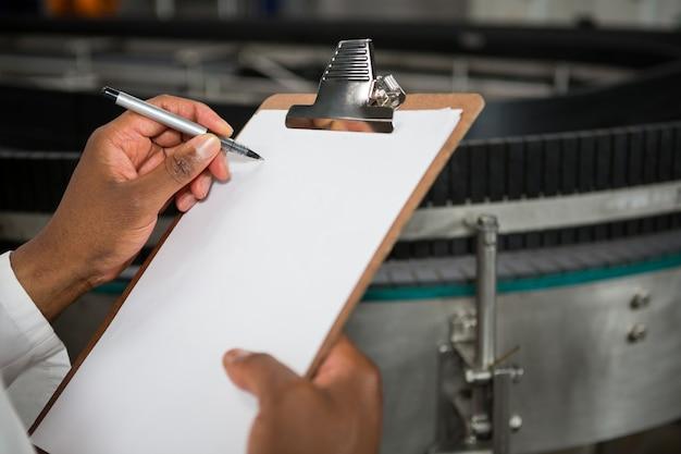 Homme notant sur le presse-papiers à l'usine de jus