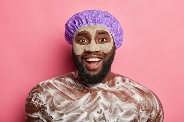 Un homme nu positif porte un masque facial, a de la mousse sur le corps, aime prendre une douche et se détendre après une journée difficile, a un large sourire et une expression joyeuse, se tient à l'intérieur.
