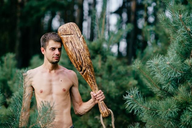 Homme nu primitif avec un énorme bâton en bois posant dans la forêt