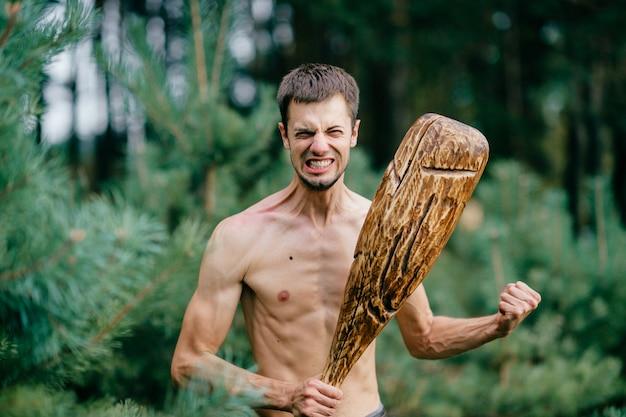 Homme nu primitif étrange avec un énorme bâton en bois chassant dans la forêt. les mâles adultes s'amusent comme une psyché folle avec un club grossier dans les mains. visage de garçon excité expressif. force masculine sauvage. guerrier cruel