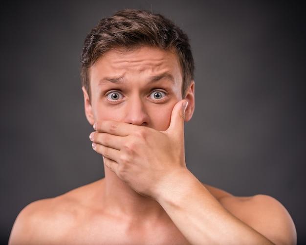Un homme nu se couvre et couvre sa bouche de sa main.