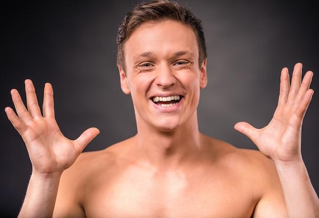 Un homme nu sourit et lève les mains.