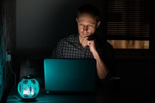 Homme la nuit avec un ordinateur portable.