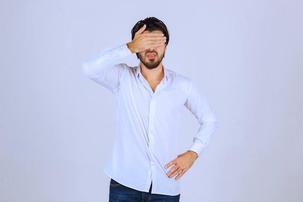 Homme observant l'extérieur à travers ses doigts ou cachant son visage.