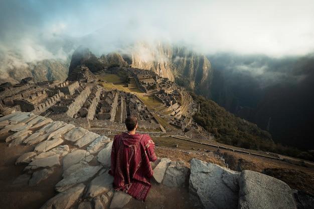 Homme observant les ruines du machu picchu